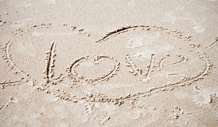 The words love written in the sand on the beach photo
