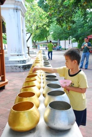 Nakhon Pathom,Thailand -September 20 2008-unidentified thai boy making merit by putting coins into buddhist monks alms Bowls at Wat Phra Pathom Jedi temple on September 20 2008 in Nakhon Pathom province-Thaland