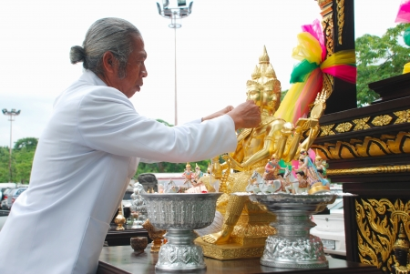 BANGKOK,THAILAND-May 26 2012: Thai brahmin priest spreading holy water to the face of statue of Brahma for setting up a new shrine in Bangkok city,Thailand on May 26 2012