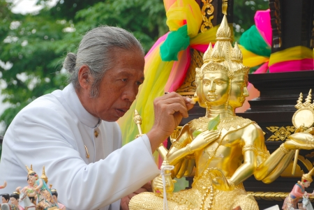 BANGKOK,THAILAND-May 26 2012: Thai brahmin priest spreading holy water to the face of statue of Brahma for setting up a new shrine in Bangkok city,Thailand on May 26 2012 Stock Photo - 14986196