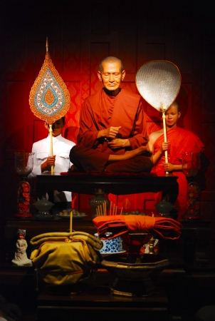 the wax statues of Thai buddhist monk meditation in sitting pose