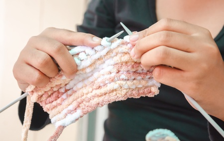 Hands of woman knitting with wool photo