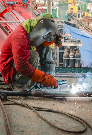welder worker welding steel pole at construction site photo