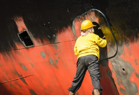 Worker cleaning side of ship at shipyard Stock Photo