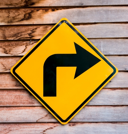 Yellow right turning traffic road sign on a wooden plank Stock Photo