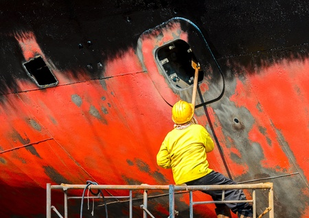 commercial dock: shipyard worker to clean ship Stock Photo