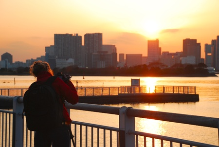 TOKYO,JAPAN-March 30:unidentified caucasian woman is adjust her camera to take a picture of sunset at Odaiba Tokyo bay on March 30,2010 in Odaiba district in Tokyo.Odaiba is a large artificial island in Tokyo Bay,Japan,across the Rainbow Bridge from centr