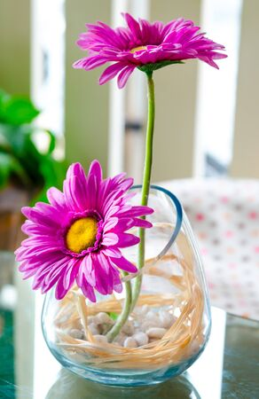 artificial flowers in jug on the table