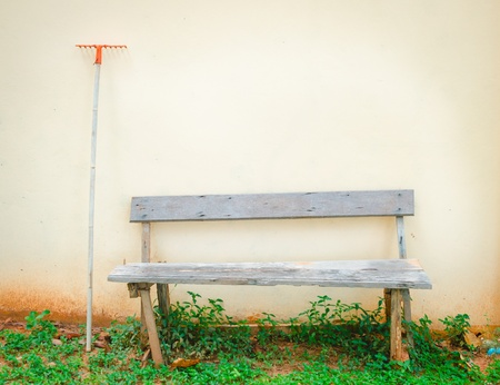 old outdoor wood bench and rake against the wall photo