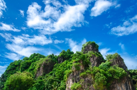 tropical rock mountain island in the sea of thailand with blue sky and clouds photo