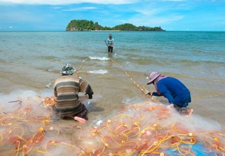 Fishermen pull up the fishing net in sea