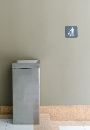 metal waste bin against a wall