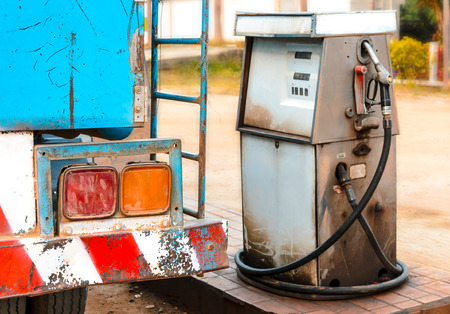 old dirty gas station pump with fuel truck photo