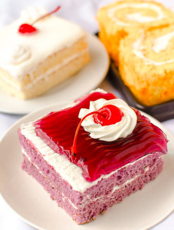 cake with mousse whipping cream and cherry on top. Shallow Depth of field with focus on the cherry