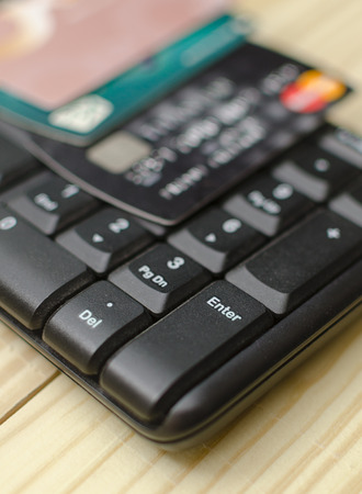 close up of a computer keyboard with credit card on top. focus on enter button