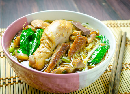 rice noodle soup with stewed chicken and vegetable in a bowl