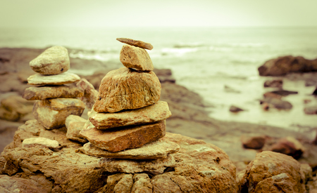 stack of stones rocks arranged at seaside coast with sepia tone effect