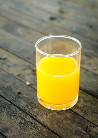 orange juice in glass on wooden background