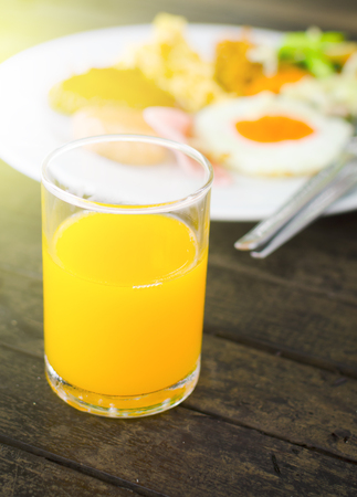 glass of orange juice and breakfast meal with soft sun light effect Stock Photo
