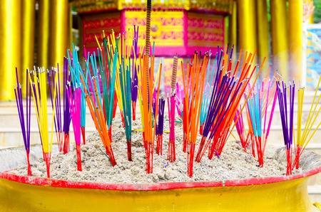 colorful of incense sticks burning in a golden pot at the temple