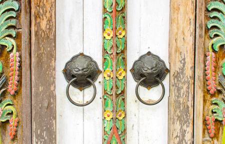 old metal antique oriental head door handle knocker on wooden door texture