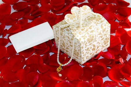 white valentine pearl gift box on rose flower petals  photo