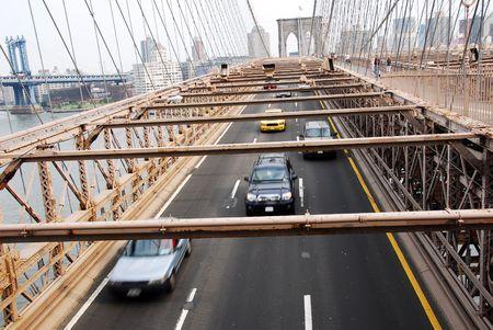 Cars and vehicles moving under Brooklyn bridge New York USA Stock Photo