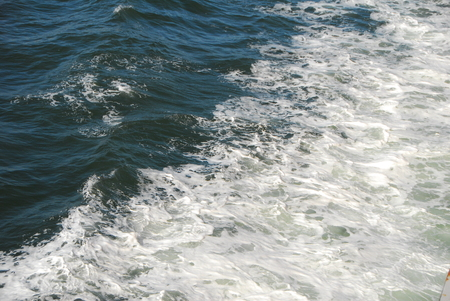 turbulence: white froth foam formation due to turbulence in sea water by moving boat Stock Photo