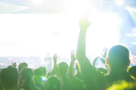 Une vue au niveau de la foule de mains levées par la foule spectatrice, entrecoupées de spots colorés et d'une atmosphère enfumée Banque d'images