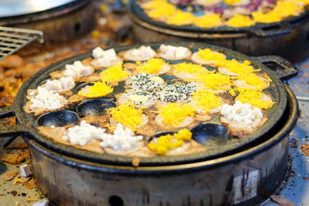 sesame street: Khanom Krok or grilled rice flour pancake with sesame, coconut and other in black hole stove , Thailand dessert. Stock Photo