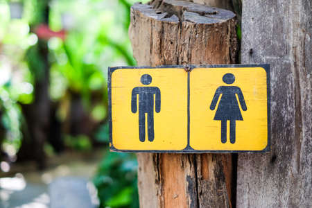 Toilet Sign (man and woman) draw on yellow sign wood for background or texture.