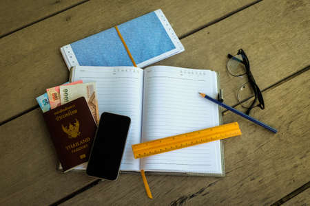 Thailand passport with money, pencil and yellow ruler for blank notebook (write your travel note), mobile phone and glasses - concept prepare to travel.