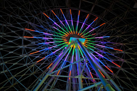 Colorful Ferris wheel at night.