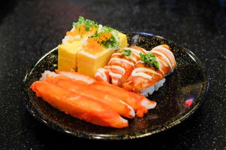 Grilled toro salmon sushi (sake nigiri) and mayonnaise top on rice, Japanese rolled omelette (tamagoyaki) with shrimp eggs (tobiko), spring onion and imitation crab stick serve on black plate. Reklamní fotografie
