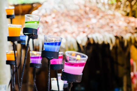 Many colorful candle in crystal glass at Ratchanikorn Candle (Ban Hom Tien) - Ratchaburi, Thailand. Stock Photo