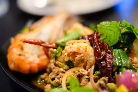 black textured background: Big shrimps and squids and spicy minced pork mixed together with various herbs and vegetables including dried chilli served on black plate, for thai food background or texture.