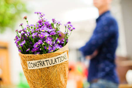 Beautiful violet or purple Gypsophila flower in brown grid paper bouquet for you with Congratulations word for wishing you all the best for your birthday or celebration concept.