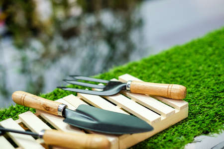 Black shovel and fork set on wooden tool box with field grass for equipment agriculture or farmland concept. Stock Photo