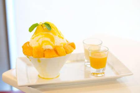 Mango kakigori (Japanese shaved ice dessert flavor with mango ice-cream) serve on white bowl with yellow mango sauce