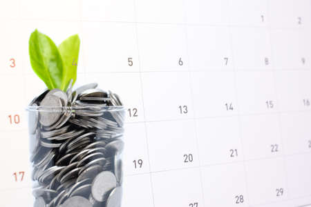 Saving (frugal) money in glass for your investment future is similar to growing green leaves on tree and write a message on calender for background or texture - economical & activity 2018 concept.