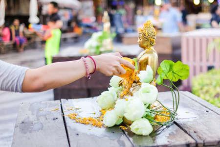Bangkok, Thailand - April 13, 2017 :  Hand pouring water to gold buddha with white lotus on Songkran Festival in Sampheng market.