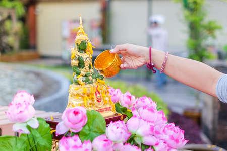 Bangkok, Thailand - April 13, 2017 :  Hand pouring water to emerald buddha with pink lotus on Songkran Festival in Sampheng market. 新聞圖片
