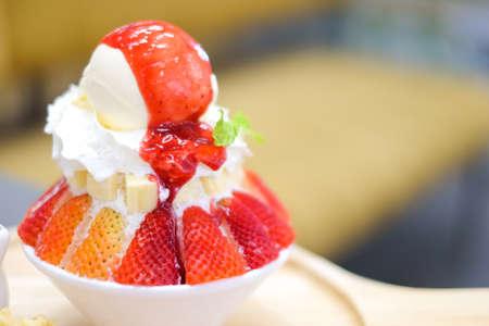 Strawberry kakigori (Japanese shaved ice dessert flavor with vanilla ice-cream) or bingsu (Korea dessert) serve on white bowl with strawberry sauce for sweet food background or texture.