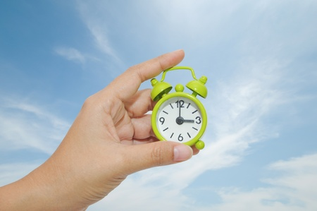 Hand and Green Alarm Clock Stock Photo - 10919570