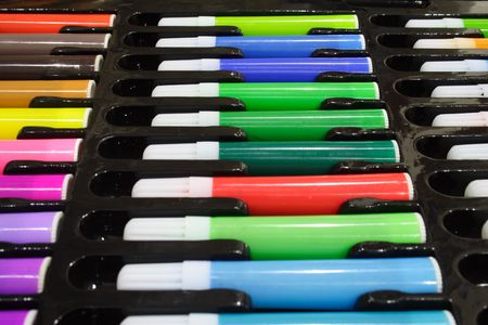 Close-up of colored marker pens on a black tray