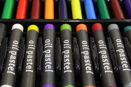 Colorful oil pastels in a black plastic tray case