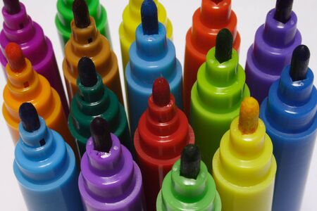 Close-up of colored markers standing with caps off