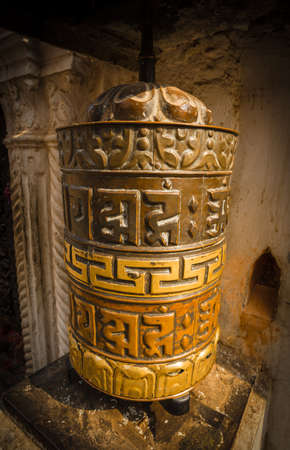 sanskrit: A prayer wheel is a cylindrical wheel made from metal, wood, stone, leather or coarse cotton. Traditionally, the mantra Om Mani Padme Hum is written in Sanskrit on the outside of the wheel. Editorial