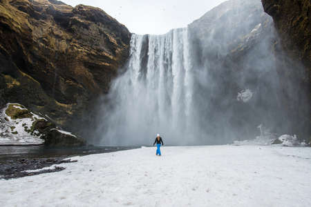 Tourist standing in front of Skogafoss one of the best known waterfalls in southern Iceland during the winter season. Stok Fotoğraf