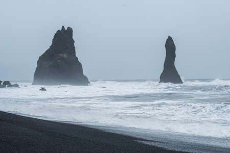 Reynisfjara or the Black Sand beach of southern Iceland with the iconic rock formation Reynisdrangar in dramatic mood and sky.